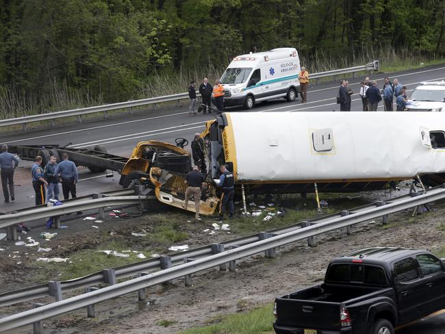 Emergency personnel work at the scene of a school bus and dump truck collision, injuring multiple people. Picture: AP