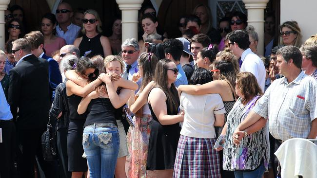 Family members and friends grieve as they watch the hearse carrying the coffin of Elyse Miller-Kennedy being driven away which was held at St Thomas Catholic Church in Mareeba. PICTURE: JUSTIN BRIERTY
