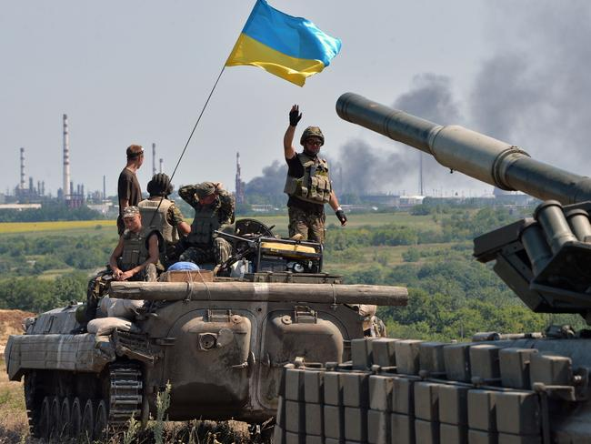Fighting back ... An armoured personnel carrier flying Ukraine's flag (L) and a Ukrainian tank, prepare for battle.