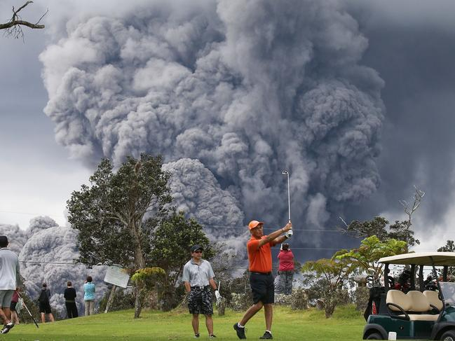 People play golf as an ash plume rises in the distance from the Kilauea volcano on Hawaii's Big Island on May 15, 2018 in Hawaii Volcanoes National Park, Hawaii. Picture: Mario Tama/Getty Images