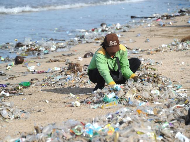A rubbish collector clearing trash on Kuta beach near Denpasar, on Indonesia's tourist island of Bali. Picture: Sonny Tumbelaka / AFP