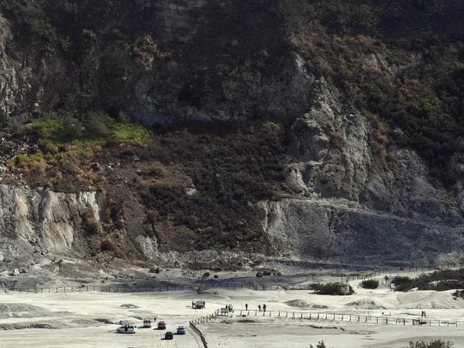 Rescuers stand on the site where three people reportedly died when they fell into a crater in a steamy volcanic field in Pozzuoli, near Naples, Italy. Picture: AP