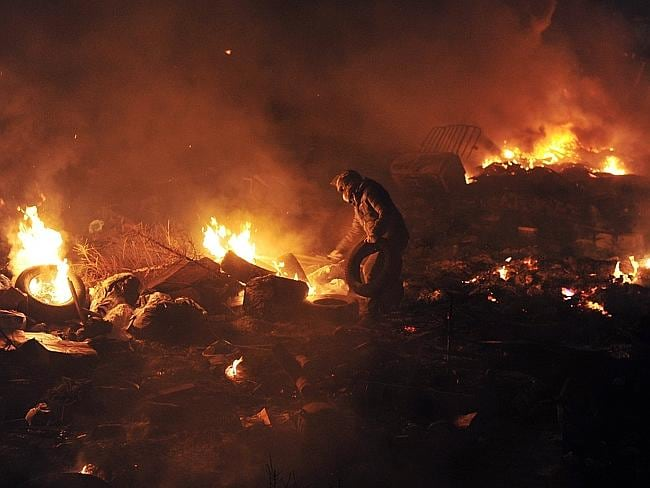A protester throws tyres to maintain a barricade of flames between protesters and police in Kiev.