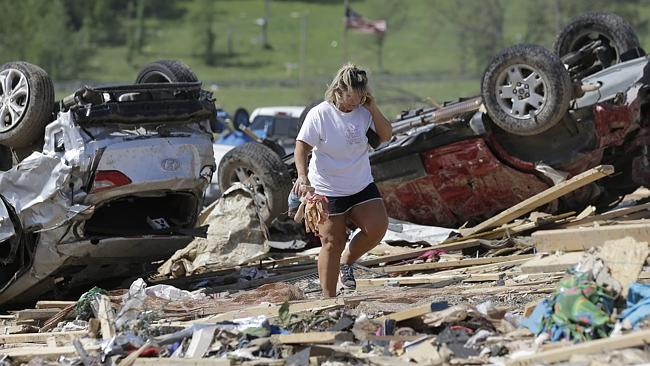 Connie Krehel looks through debris after her home was hit by a tornado, Monday, April 28, 2014, in Vilonia, Arkansas. Picture: AP