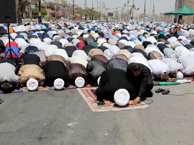 Life goes on . followers of Shiite cleric Muqtada al-Sadr attend open-air Friday prayers in the Shiite stronghold of Sadr City, Baghdad. Picture: Karim Ka
