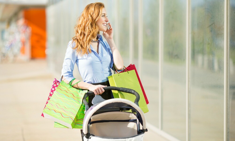 Cheerful mother shopping outdoors and pushing baby stoller.