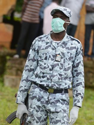 An Ivorian policeman wears a mask and gloves to protect himself from the Ebola virus, near the border with Guinea and Liberia. Picture: Issouf Sanogo