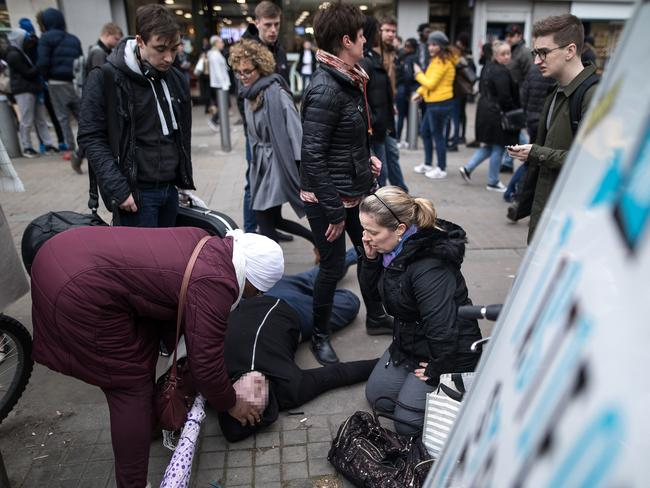 Passers-by tend to a drug-affected man in Manchester's shopping hub. Picture: Joel Goodman/LNP