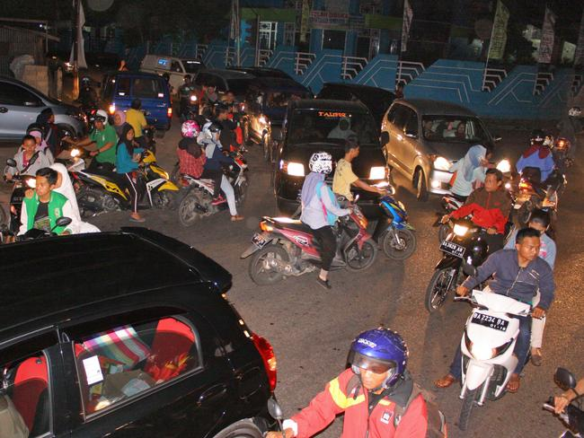 Chaotic traffic is seen on a street as people try to reach higher ground. Picture: AP
