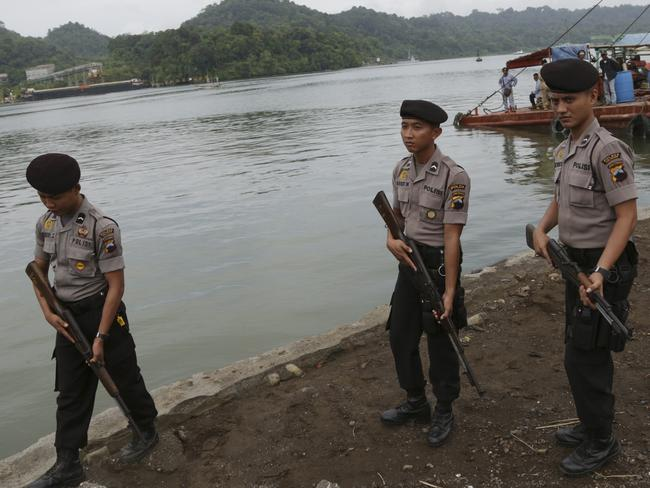 On guard ... Indonesian police stand guard in Cilacap, Central Java, Indonesia as a ferry with Indonesian police armoured vehicles carrying Andrew Chan and Myuran Sukumaran arrives at Nusakambangan island. Picture: AP