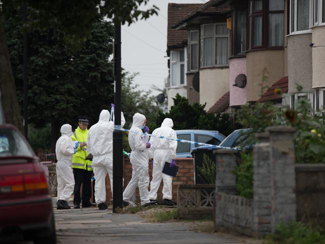Forensic investigators examine a property in Edmonton where a woman is thought to have been beheaded. Picture: Oli Scarff/Getty Images