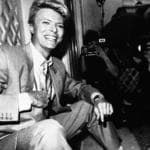Pop star David Bowie, wearing a business suit, smiles while being photographed at a press reception May 22, 1983, at London's Claridge Hotel. Bowie, once the glitter-garbed Ziggy Stardust, the enigmatic man who fell to Earth, and the wigged-out thin and freakish singer who fled Los Angeles, has metamorphosed again. (AP Photo)