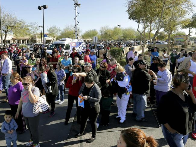 Anxious wait ... Parents wait to reunite with their children outside Independence High School. Picture: Matt York/AP
