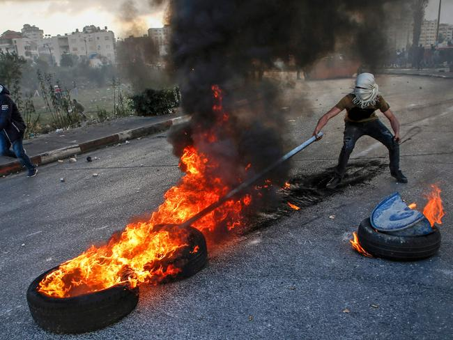 A Palestian protester uses a stick to move flaming tyres during clashes with Israeli security forces near the West Bank checkpoint of Qalandia, on the outskirts of Ramallah. Picture: AFP