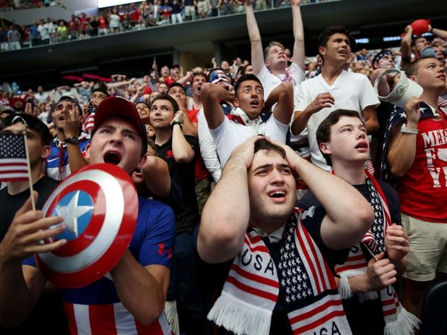 Josh Kerber, center, of Dallas, reacts with other fans after a missed opportunity by the United States.