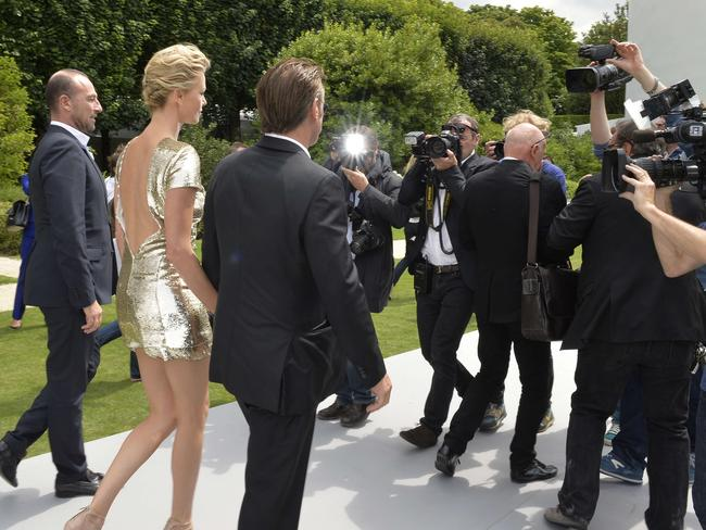 Super sexy ... Charlize Theron and companion Sean Penn making a stunning entrance at the Dior show in Paris.