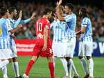 Adelaide United's Marcelo Carrusca walks past Malaga players celebrating their first goal. Picture: Sarah Reed.