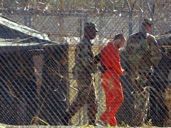 Detained ... David Hicks being escorted by US military police at Camp X-Ray Naval Base in Guantánamo Bay in Cuba in 2002. Picture: Supplied