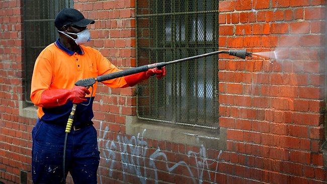 City of Yarra Council crewman Gahak Thuol cleans graffiti from brick walls in Collingwood. Picture: Tim Carrafa
