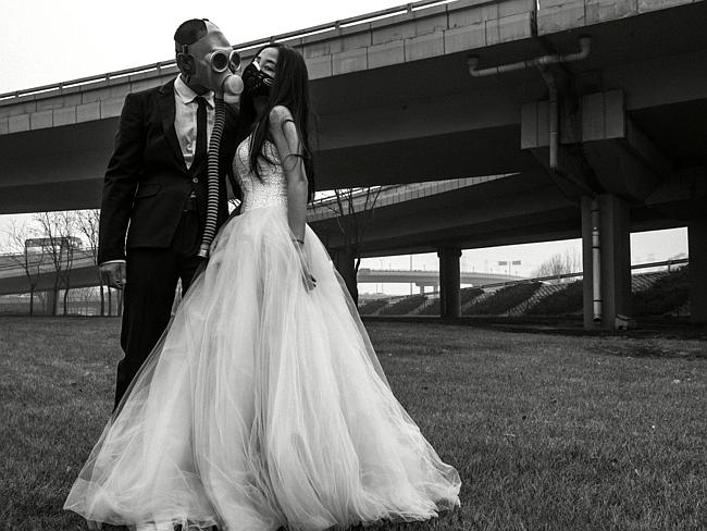 Wedding kiss? ... The newlyweds pose in their wedding outfits and gas masks under a highway in Beijing. Picture: Austral: Source: Supplied