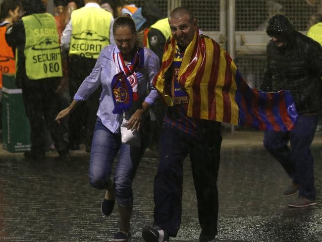 Supporters battle heavy rain before the group D Champions League soccer match