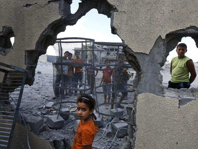 Air-strike ... Palestinian Suma Abu Mahsen, 7, stands by a damaged wall of a house following an overnight Israeli missile strike.