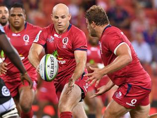 Reds player Stephen Moore passes to James Slipper during the 1st round Super Rugby match between the Queensland Reds and the Sharks from South Africa, at Suncorp Stadium in Brisbane, Friday, Feb. 24, 2017. (AAP Image/Dave Hunt) NO ARCHIVING, EDITORIAL USE ONLY