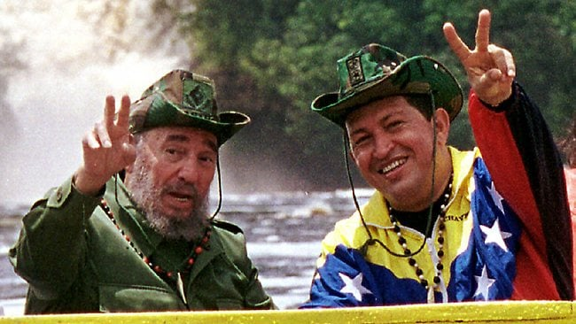 Cuba's President Fidel Castro and Venezuela's President Hugo Chavez wave to a crowd during a 2011 tour of Canaima National Park in eastern Venezuela in a canoe. Picture: Miraflores Presidential Palace/AP