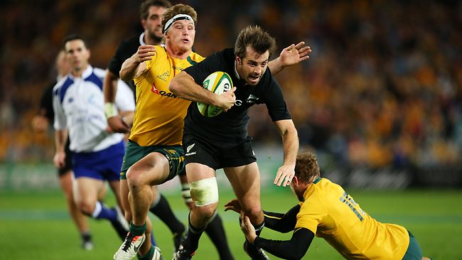 All Blacks centre Conrad Smith breaks through the tackle of Wallabies fullback Jesse Mogg and flanker Michael Hooper. Picture: Brendon Thorne