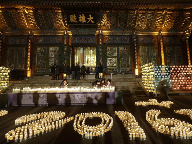 Buddhists light candles during New Year celebrations at Jogye Buddhist temple in Seoul.