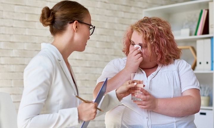 Portrait of beautiful female psychiatrist handing glass of water to crying obese woman during group therapy session, providing counseling and support on mental issues
