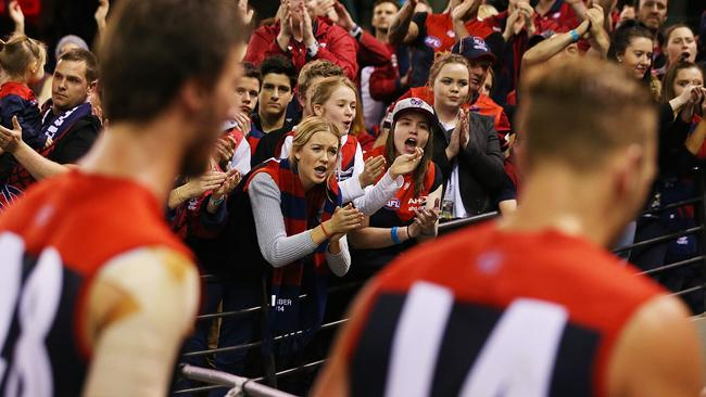 Melbourne players are cheered off by their fans.
