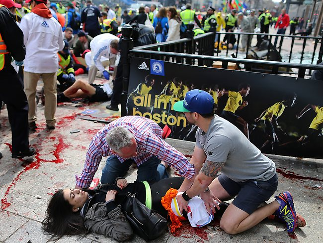 An injured woman is tended to at the finish line. Picture: AP