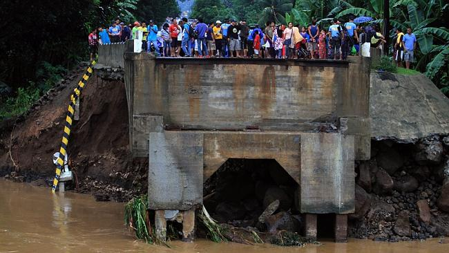 Residents stand on the edge of a bridge destroyed by flooding brought about by heavy rains in Linamon town, Lanao del norte province, in southern island of Mindanao. Picture: AFP
