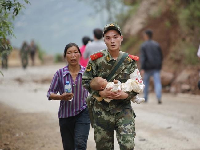 Emergency ... a Chinese rescuer carries a baby after an earthquake hit China's Yunnan province, killing at least 175 and injuring 1700 more. Picture: AFP