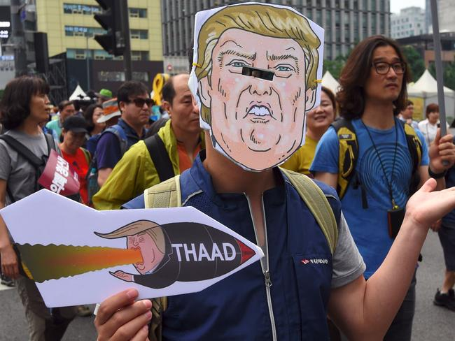 A South Korean protester wearing a mask of US President Donald Trump marches toward the US embassy during a rally against the deployment of the US Terminal High Altitude Area Defense (THAAD) system in Seoul in June. Picture: AFP