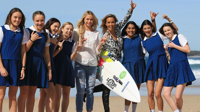 Surfer Sally Fitzgibbons on Cronulla beach with Macy Callaghan and young surfers from Woolooware High School.