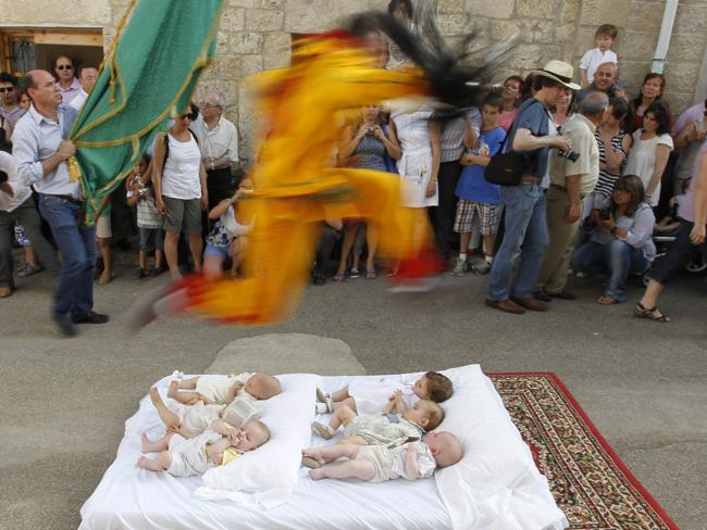 A man dressed up as the devil jumps over babies lying on a mattress in the street during El Colacho, the baby jumping festival on June 26, 2011 in the village of Castrillo de Murcia, near Burgos. Baby jumping (El Colacho) is a traditional Spanish practice dating back to 1620 that takes place annually to celebrate the Catholic feast of Corpus Christi. AFP PHOTO / CESAR MANSO