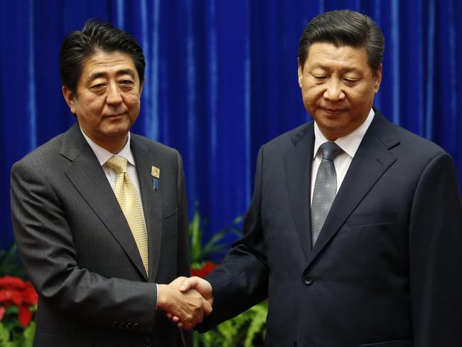 China's President Xi Jinping (right) shakes hands with Japan's Prime Minister Shinzo Abe at the Great Hall of the People on the sidelines of the Asia-Pacific Economic Cooperation (APEC) Summit in Beijing.