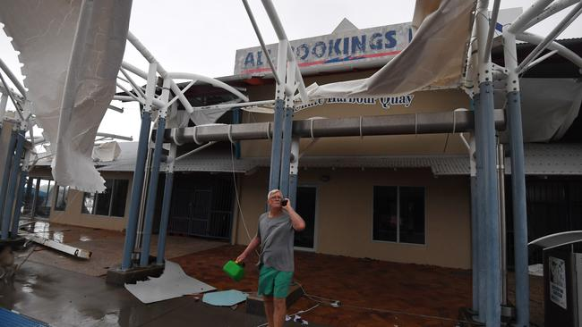 A local inspects damage to a boat terminal at Shute Harbour, Airlie Beach. Picture: AAP.