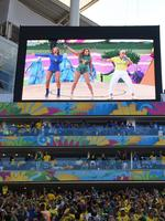 Brazilian fans watch as Brazilian singer Claudia Leiite, US singer Jennifer Lopez and US rapper Pitbull (on the screen from L-R) perform during the opening ceremony of the 2014 FIFA football World Cup at the Corinthians Arena in Sao Paulo on June 12, 2014. AFP PHOTO / VANDERLEI ALMEIDA