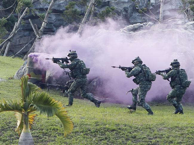 Soldiers from Taiwan's special forces move past colored smoke during a helicopter landing training and all-out defense demonstration in Taipei last week. Picture: AP