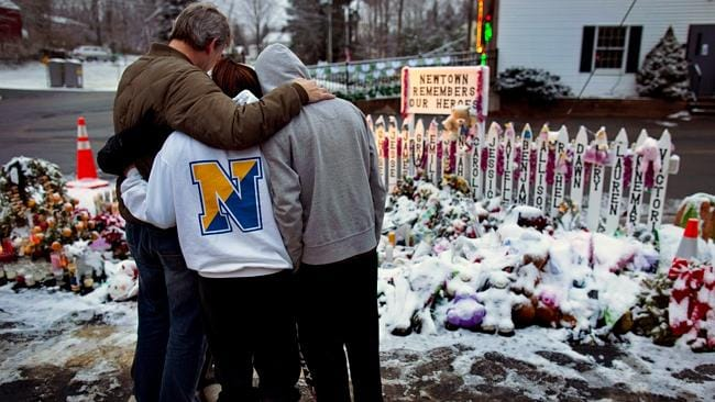 Never forget ... People stand near memorials by the Sandy Hook firehouse in Newtown, Connecticut, which spells out the names of Adam Lanza's victims.
