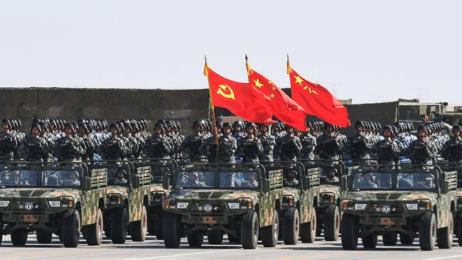 Chinese soldiers carry the flags of (L to R) the Communist Party, the state, and the People's Liberation Army during the military parade at the Zhurihe training base in China's northern Inner Mongolia region. The parade marked the 90th anniversary of the People's Liberation Army. Picture: AFP