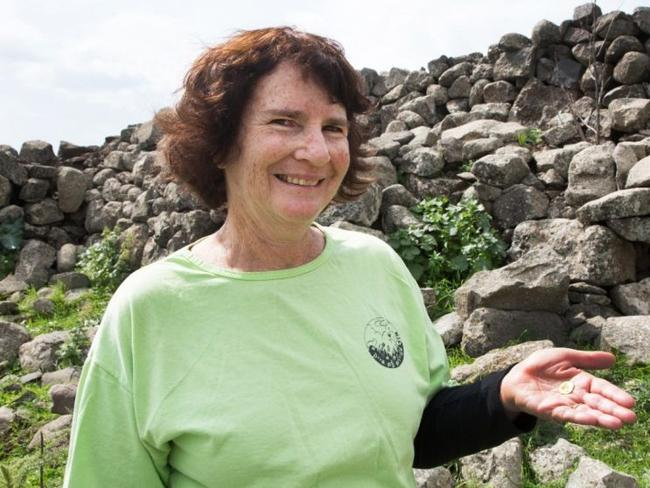 Laurie Rimon with the coin. Picture: Samuel Magal, courtesy of the Israel Antiquities Authority