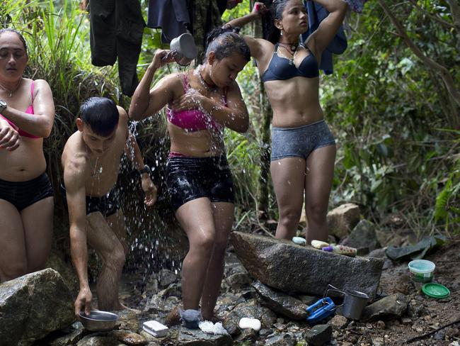 Fighters bathe in a creek near their hidden camp in Antioquia state, in the northwest Andes of Colombia. The rebel fighters share all facilities on equal terms. Many of them are couples and share sleeping quarters.