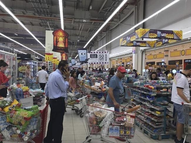 Shoppers stock up on supplies at a supermarket in Doha, Qatar on Monday. Picture: Doha News via AP
