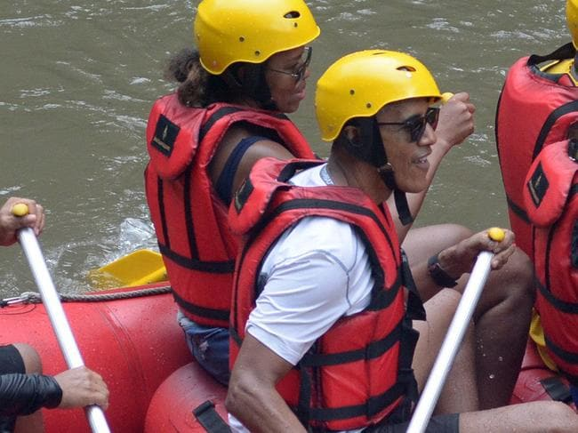 Former US president Barack Obama (3rd L), his wife Michelle (2nd L) and his daughters Sasha (front C) and Malia (R) go rafting at Bongkasa Village in Badung on Bali island on June 26, 2017.   Barack Obama kicked off a 10-day family holiday in Indonesia that will take in Bali and Jakarta, the city where he spent part of his childhood, officials said on June 24. / AFP PHOTO / STR
