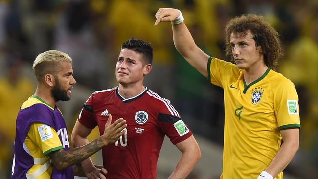 Colombia's midfielder James Rodriguez in tears is comforted by Davis Luiz and Dani Alves.