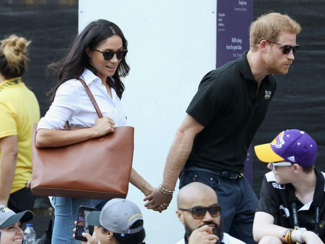 Prince Harry and Meghan Markle hold hands as they walk through the crowd. Picture: Chris Jackson/Getty Images for the Invictus Games Foundation